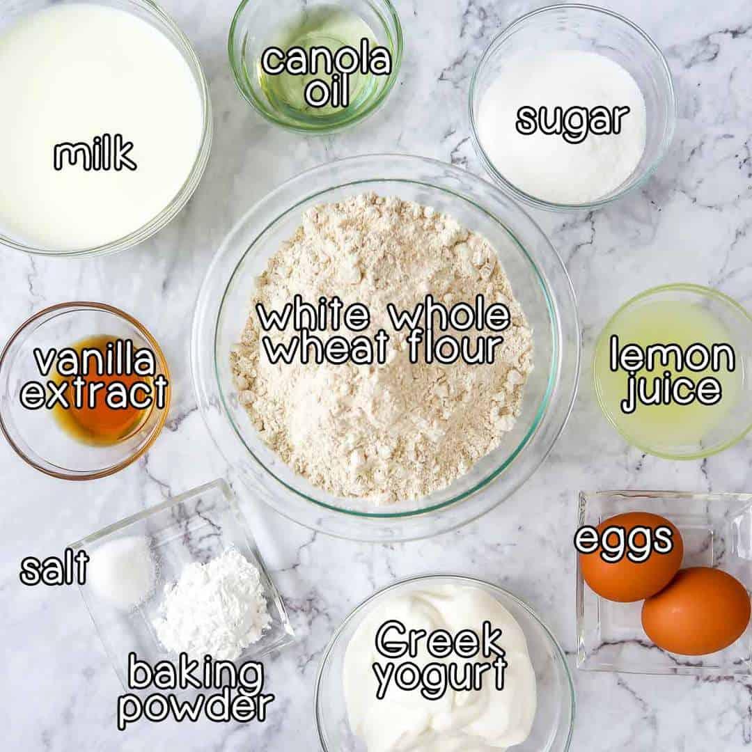 Overhead shot of ingredients- white whole wheat flour, canola oil, sugar, lemon juice, eggs, greek yogurt, baking powder, salt, vanilla extract, and milk.