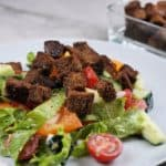 Front view of pumpernickel croutons on a lettuce and tomato salad. The salad is on a grey plate