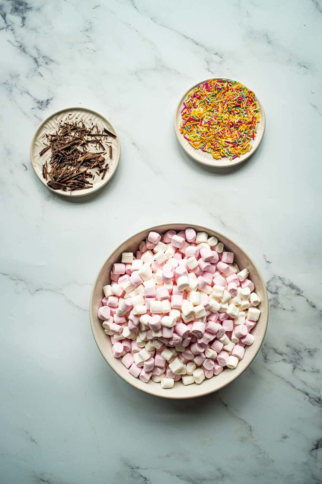 Bowls of marshmallows, sprinkles and chocolate shavings.