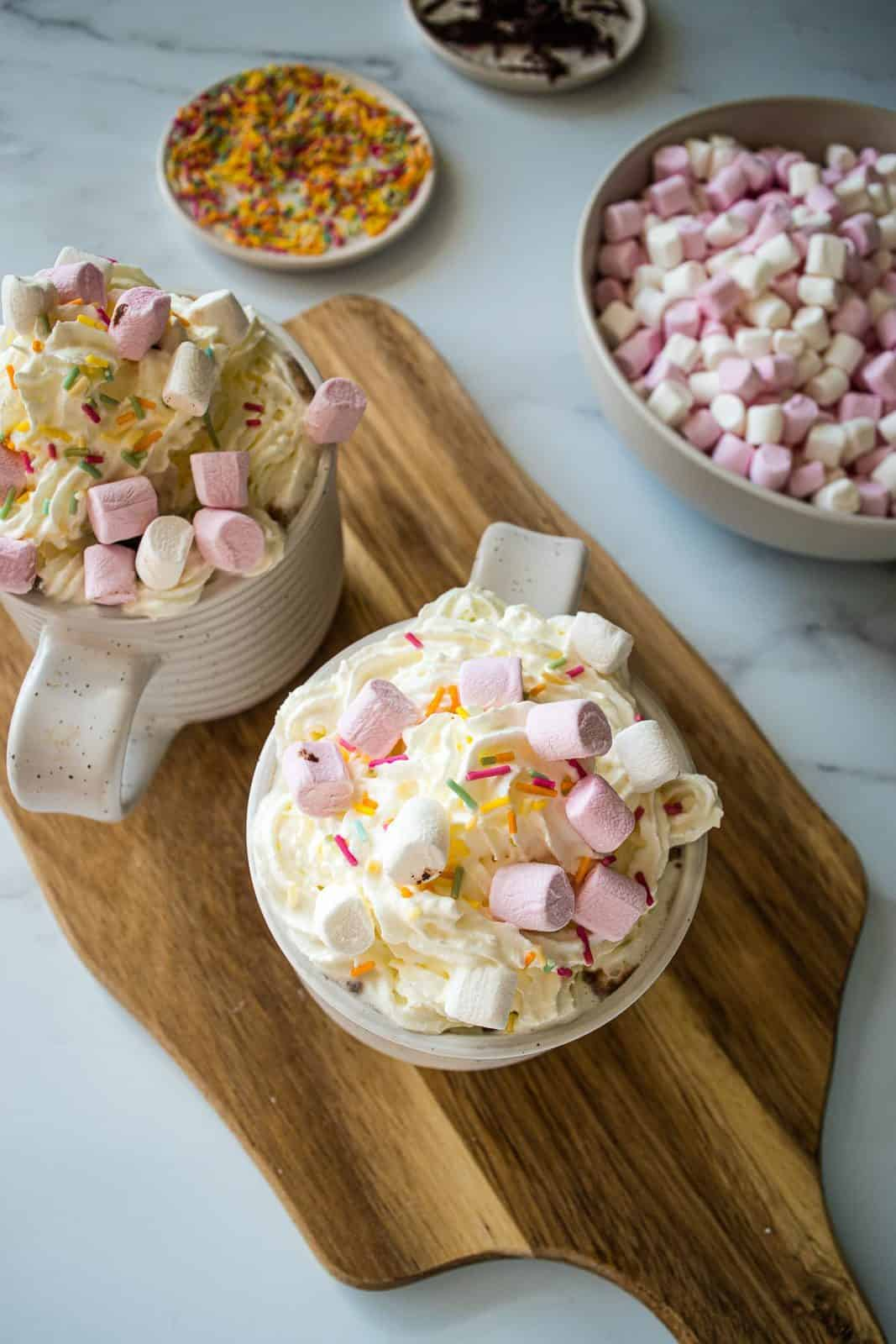 Two cups of hot chocolate topped with whipped cream and marshmallows, with bowls of sprinkles and marshmallows in the back.