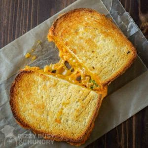 Overhead view of an oven-grilled cheese sandwich showing a gooey, stretchy cheese pull.