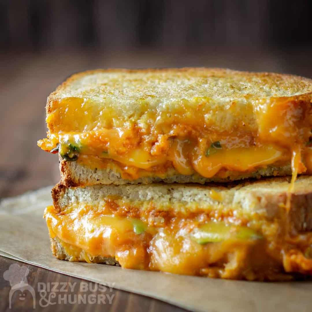Stacked grilled cheese shows the yummy cheese and pumpkin filling oozing out.