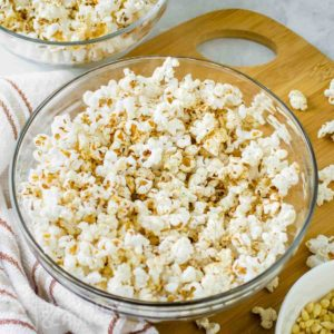 Close up shot of popcorn with homemade seasoning in a clear bowl on a wooden cutting board with popcorn sprinkled around.