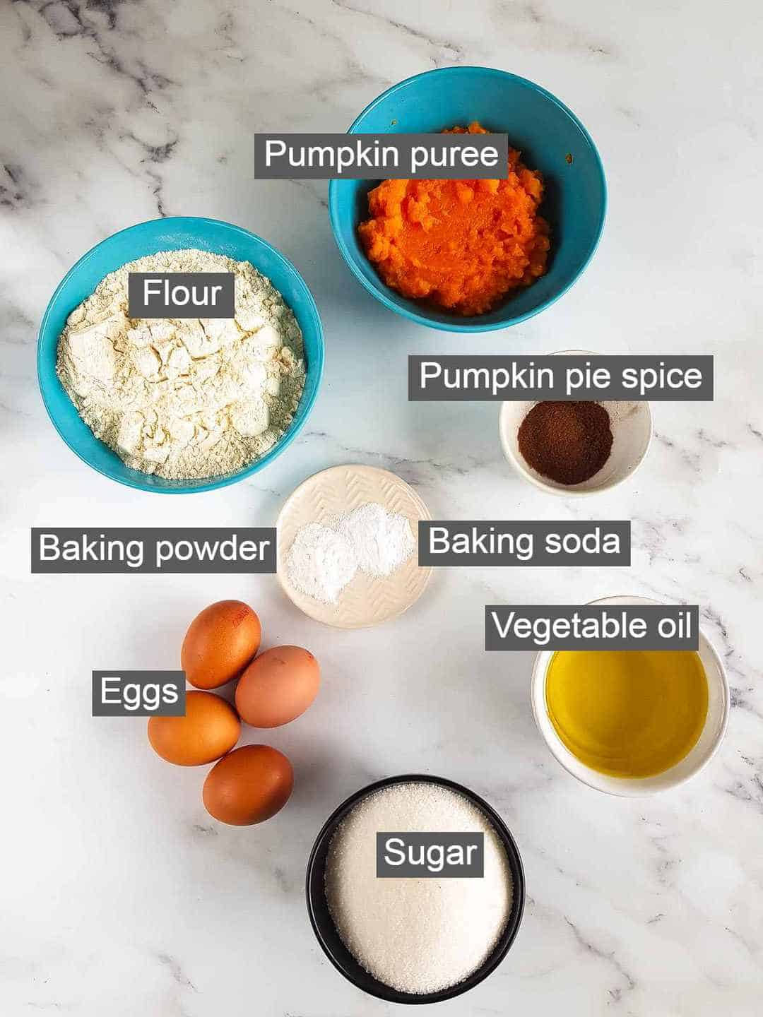 Ingredients needed for pumpkin spice cake laid out on a table.
