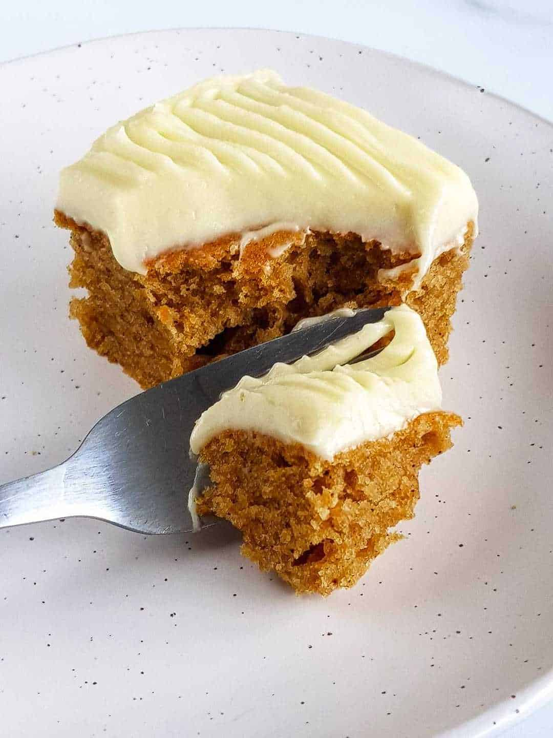 Pumpkin spice cake on a plate, with a fork cutting of a piece.