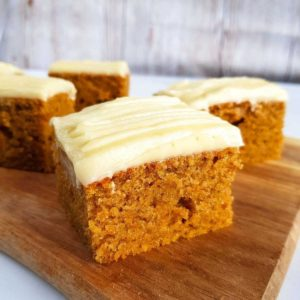 Pumpkin spice cakes with cream cheese frosting on a chopping board.