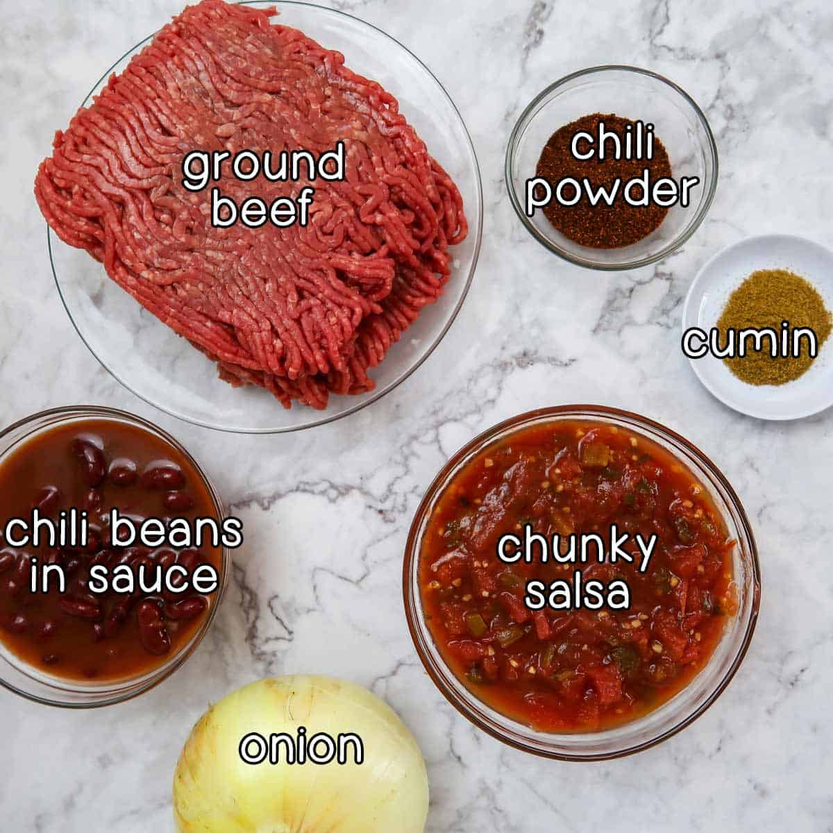Overhead shot of ingredients- ground beef, chili powder, cumin, chili beans in sauce, chunky salsa, and an onion.