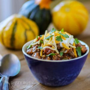 Side view of chili with salsa in a small blue bowl with a spoon on the side and colorful pumpkins in the background.