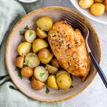 bowl of instant pot chicken breasts with a side of potatoes