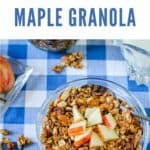 Overhead view of a bowl of granola with chopped apples on a blue checked tablecloth.