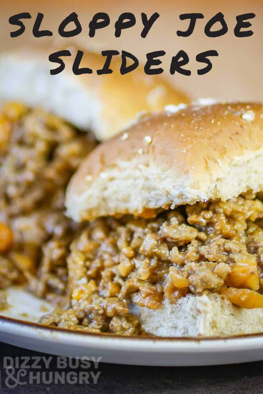 Close up shot of two sloppy joe sliders on a white plate.