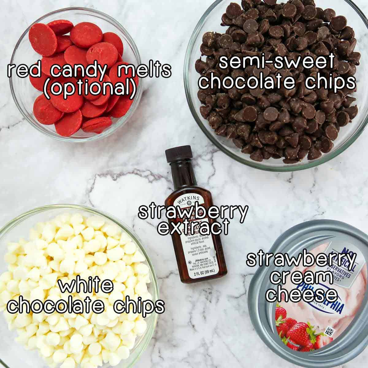 Overhead shot of ingredients- Red candy melts, semi-sweet chocolate chips, white chocolate chips, strawberry cream cheese, and strawberry extract.