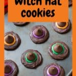 Overhead view of multiple completed cookies on a dark baking tray with text that says Witch Hat Cookies.