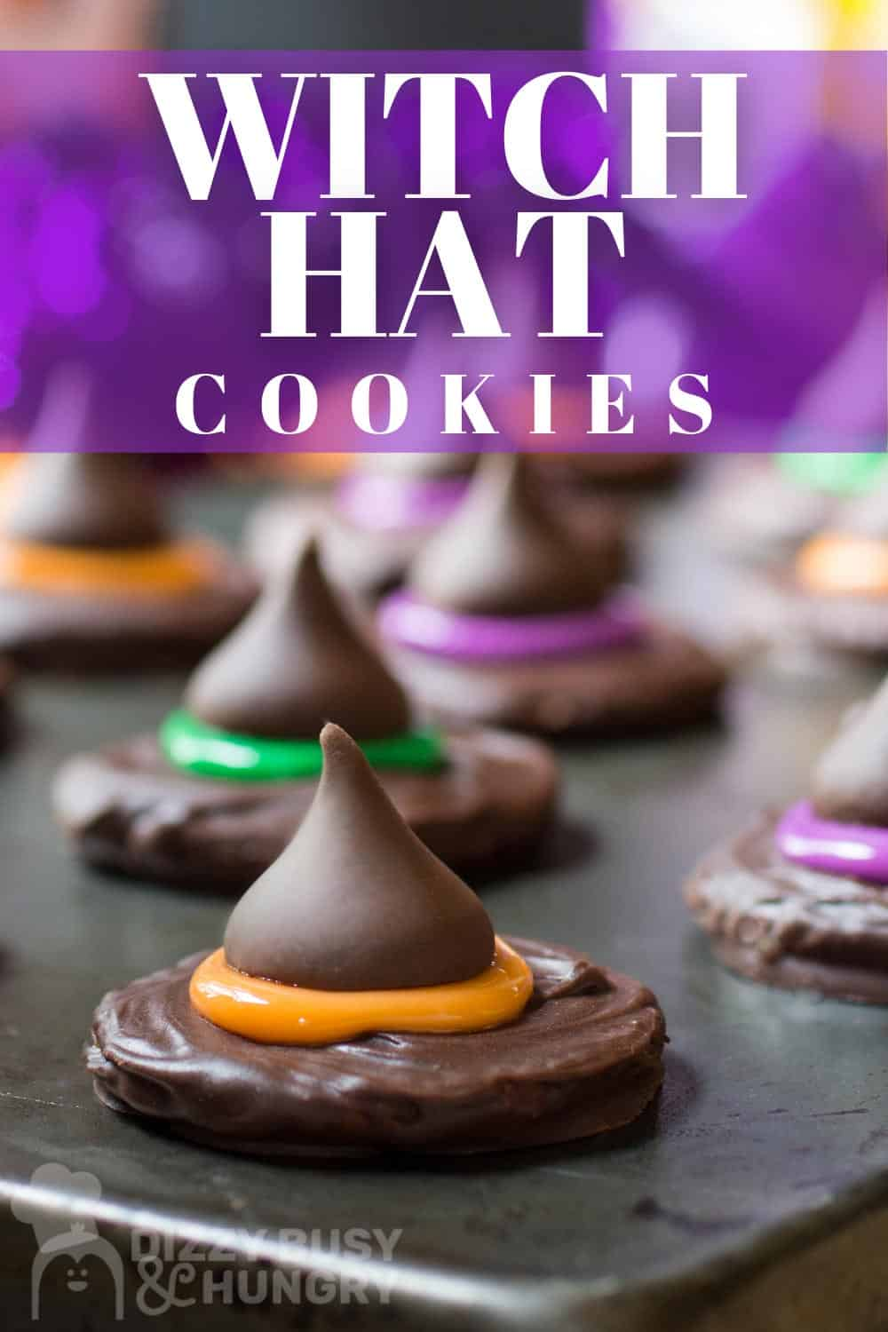 Close up view of a witch hat cookie with an orange hat band on a dark tray.