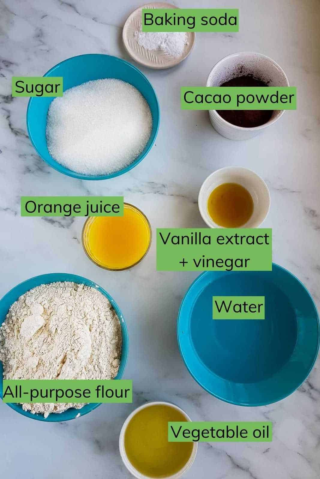 The ingredients to make chocolate cake laid out on a table.