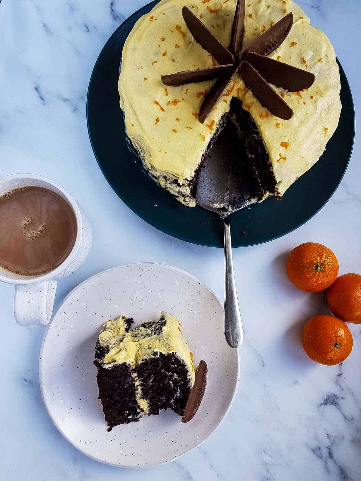 A chocolate orange cake with a slice cut out and placed on a plate.