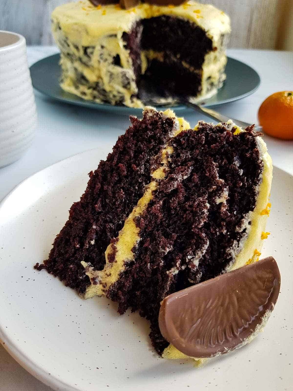 Close up of a slice of chocolate cake with orange frosting.