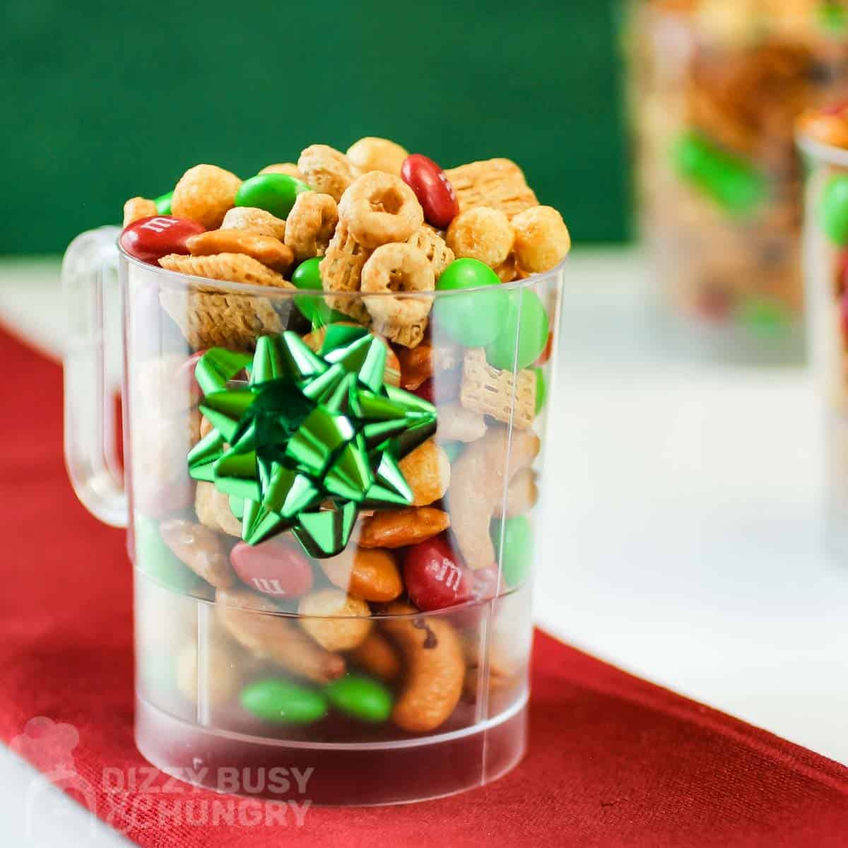 Side view of Christmas snack mix in a clear mug with a green bow on a red cloth.