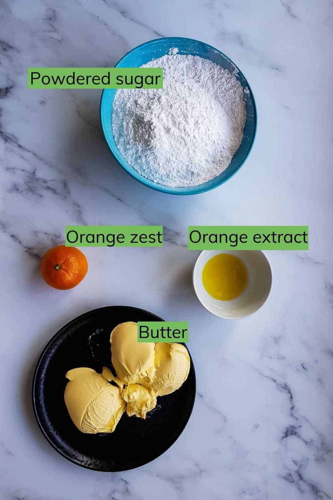 Ingredients for orange frosting laid out on a table.