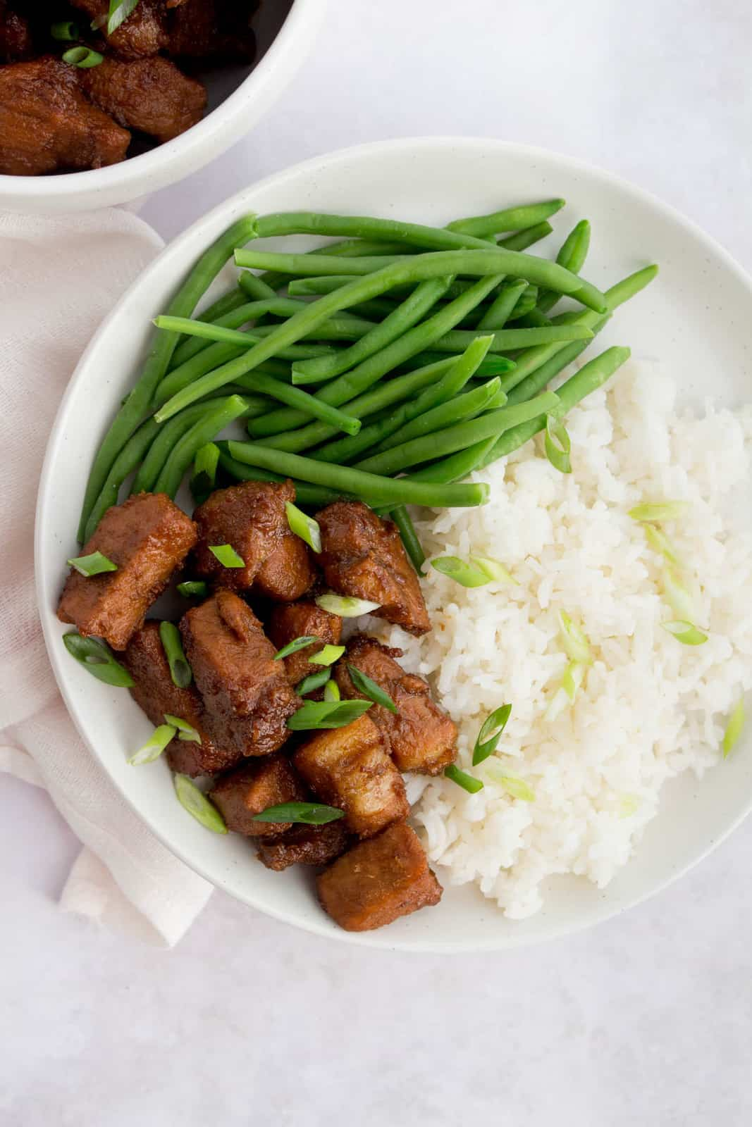 Close up overhead photo of braised garlic and soy pork and green beans with rice on a white plate.