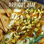 Close up view of baked brie with pita chips, apricots, and herbs in a skillet on a wooden surface.