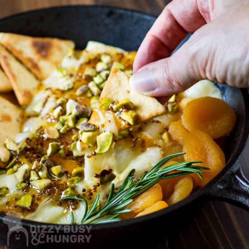 Close up shot of a pita cracker being dipped into baked brie with more crackers, apricots, and herbs on the side in a skillet on a wooden surface.
