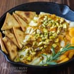 Close up shot of baked brie in a skillet with pita chips, apricots and herbs surrounding it on a wooden surface.