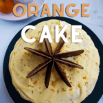 a picture of a cake with orange buttercream, decorated with chocolate orange slices and a text decoration that says