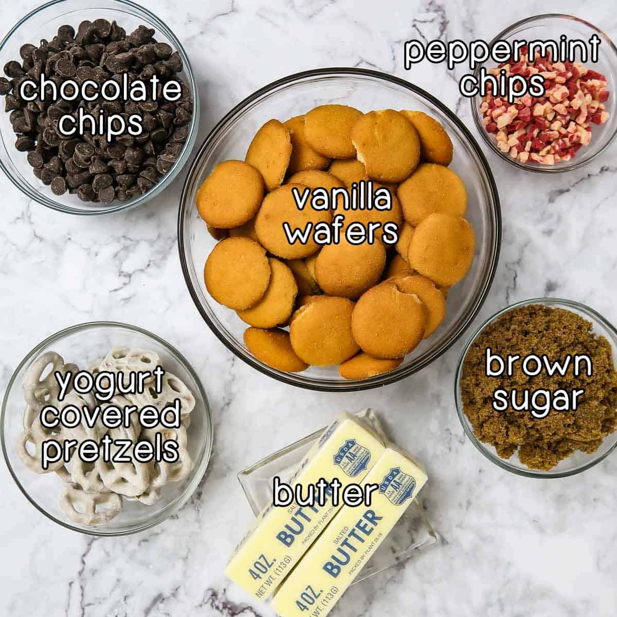 Overhead shot of ingredients- vanilla wafers, peppermint chips, brown sugar, butter, yogurt covered pretzels, and chocolate chips.