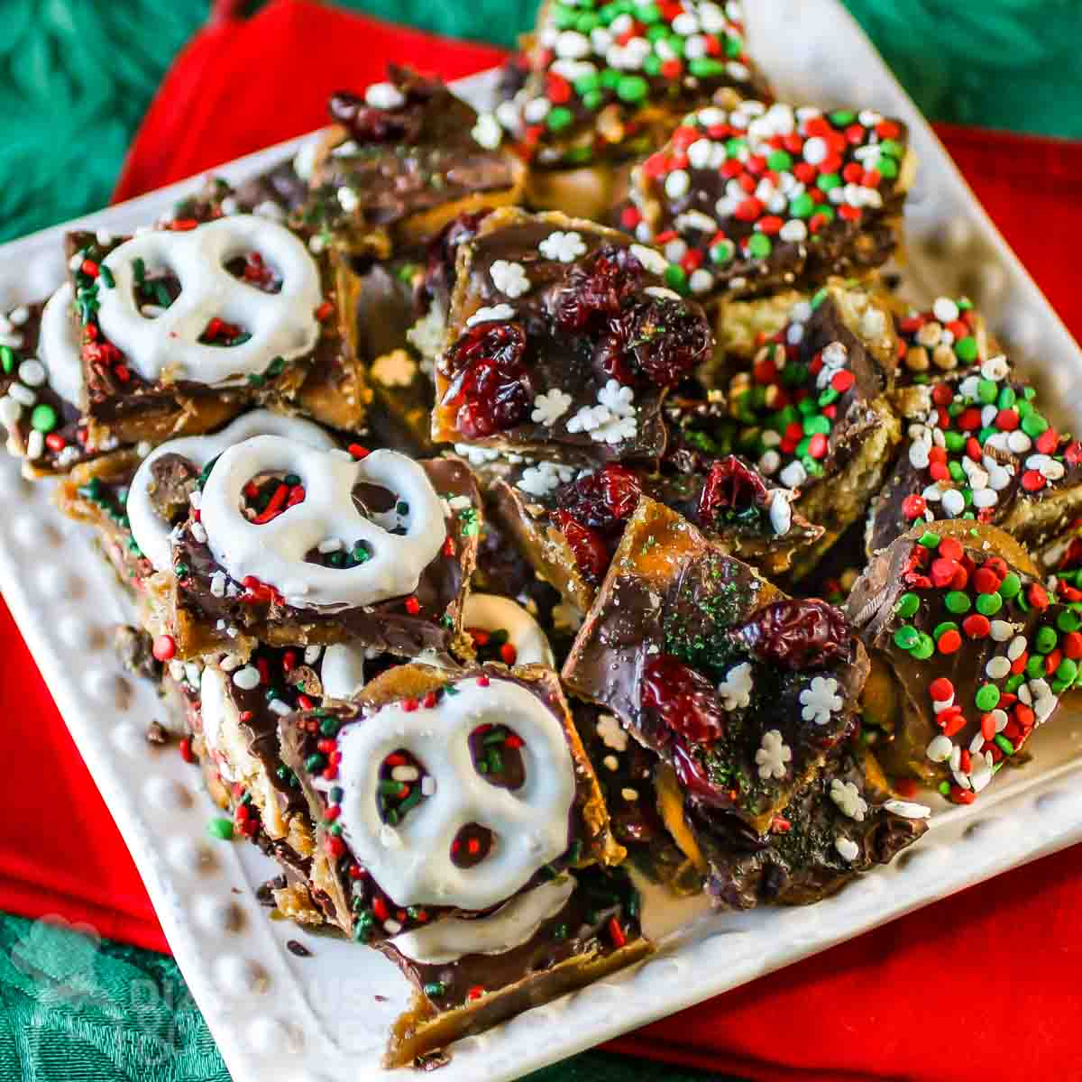 Overhead shot of Christmas bark pieces on a white square plate on a red and green cloth.