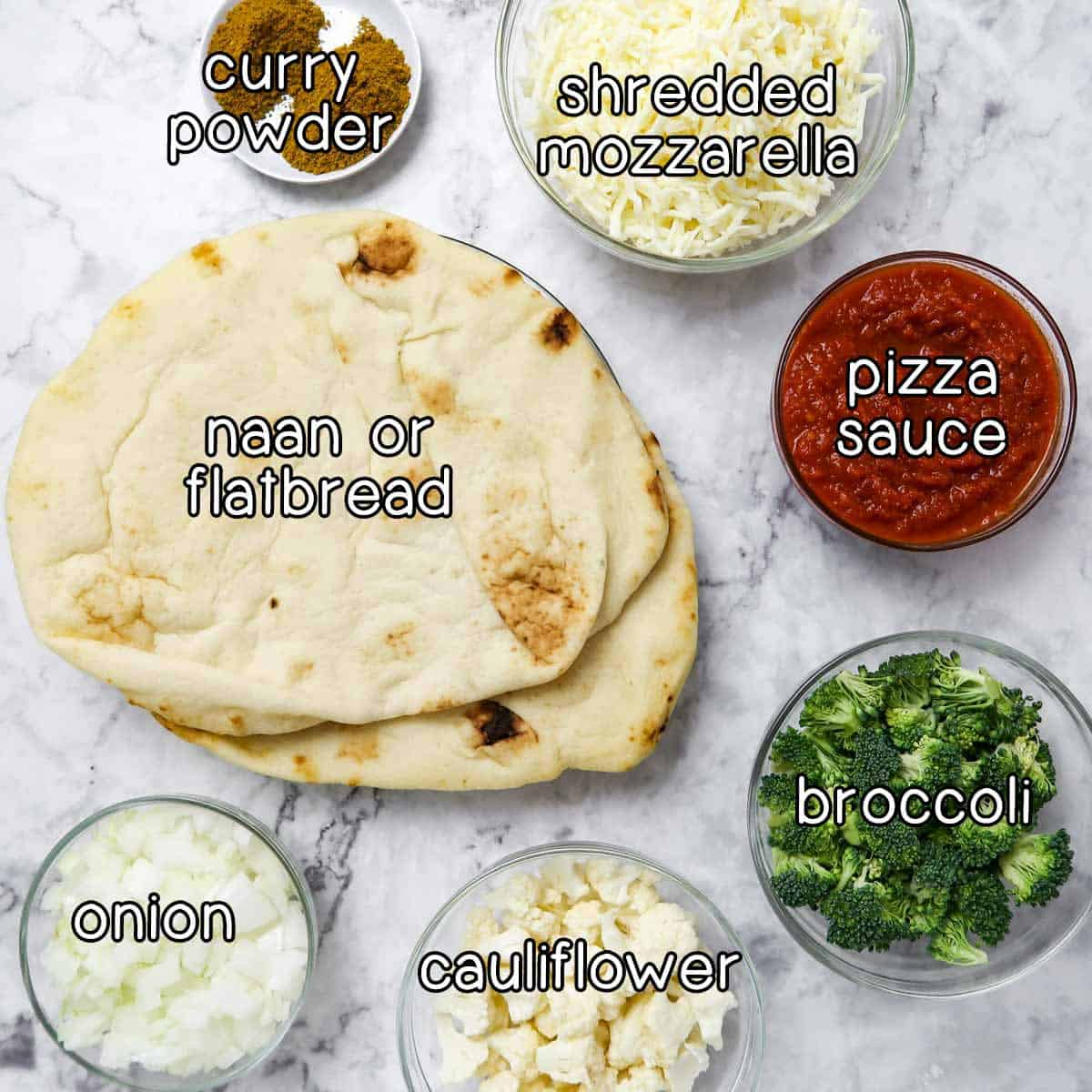 Overhead shot of ingredients- naan or flatbread, curry powder, shredded mozzarella, pizza sauce, broccoli, cauliflower, and onion.