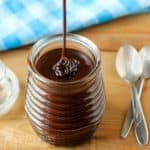 Side view of chocolate sauce being drizzled into a clear glass with a blue plaid cloth and spoons in the background.