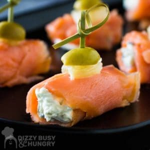 Side view of multiple smoked salmon bites on a black plate.