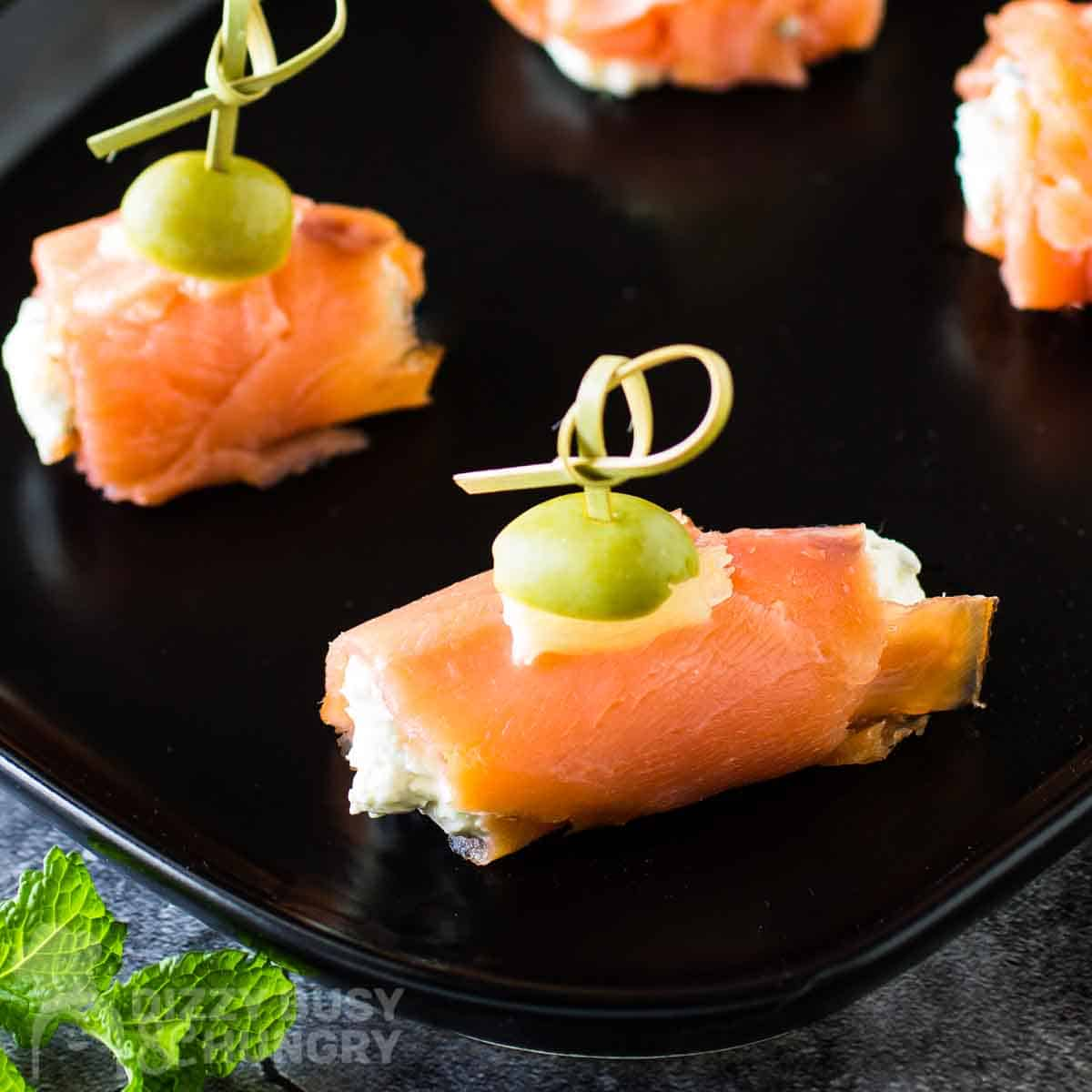 Overhead side view of smoked salmon bites on a black plate with herbs on the side.
