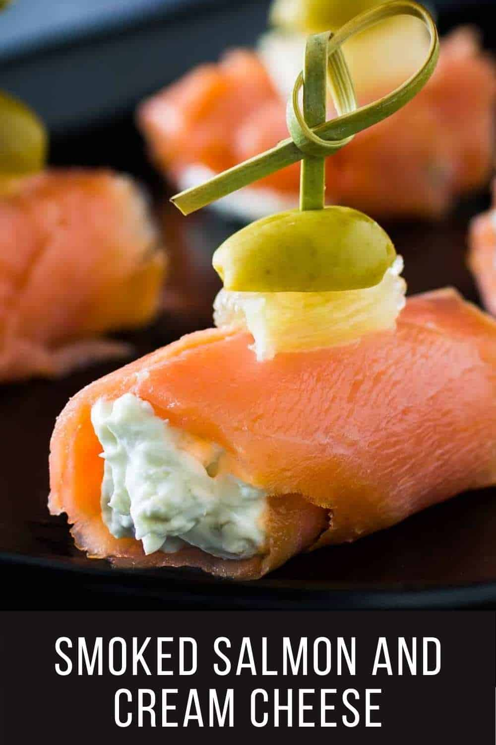 Close up shot of multiple smoked salmon bites on a black plate.