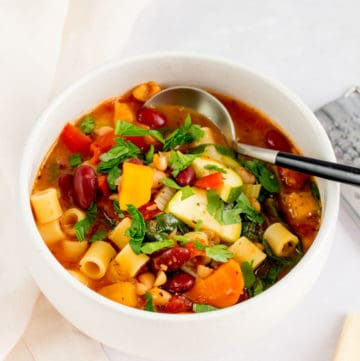 A white bowl with vegetarian minestrone with a spoon inside.