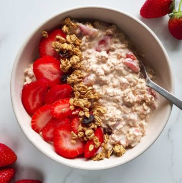 Overnight oats with strawberries, topped with granola and fresh berries.