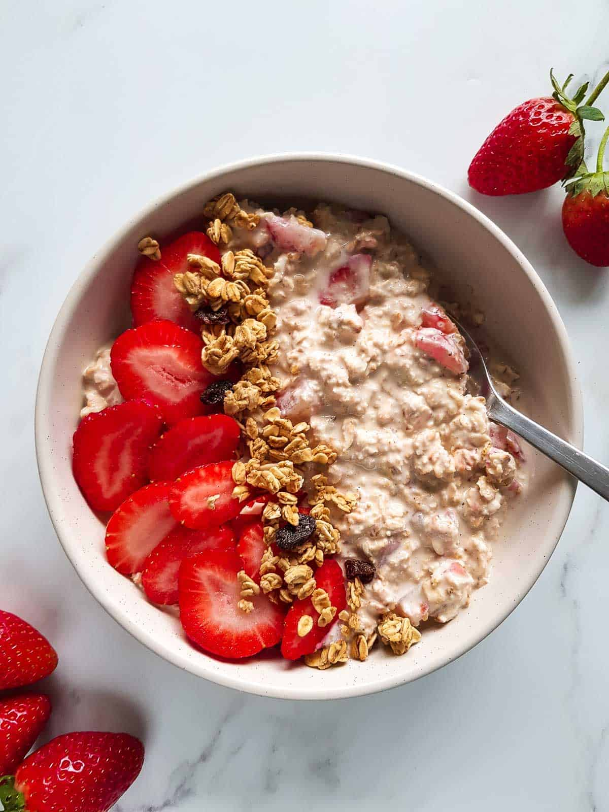 A bowl of strawberry overnight oats topped with strawberries and granola.