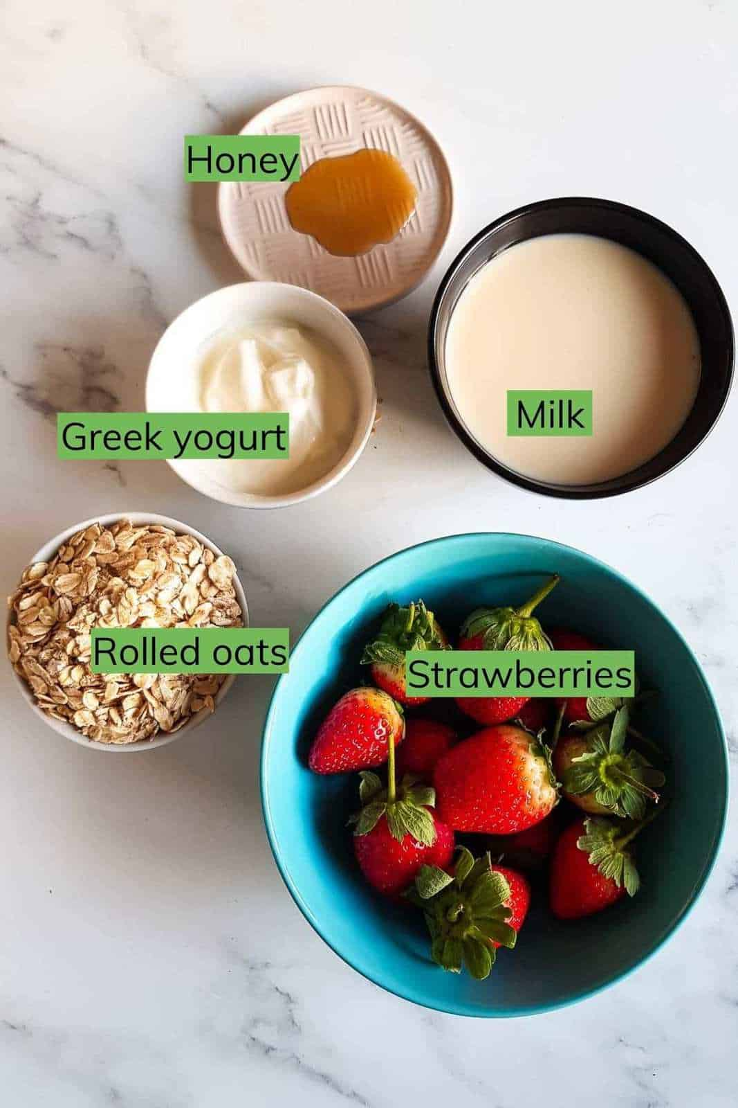 All the ingredients needed to make strawberry overnight oats laid out on a table.