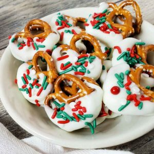 Overhead view of Christmas pretzels on a white plate sitting on a weathered wooden table.
