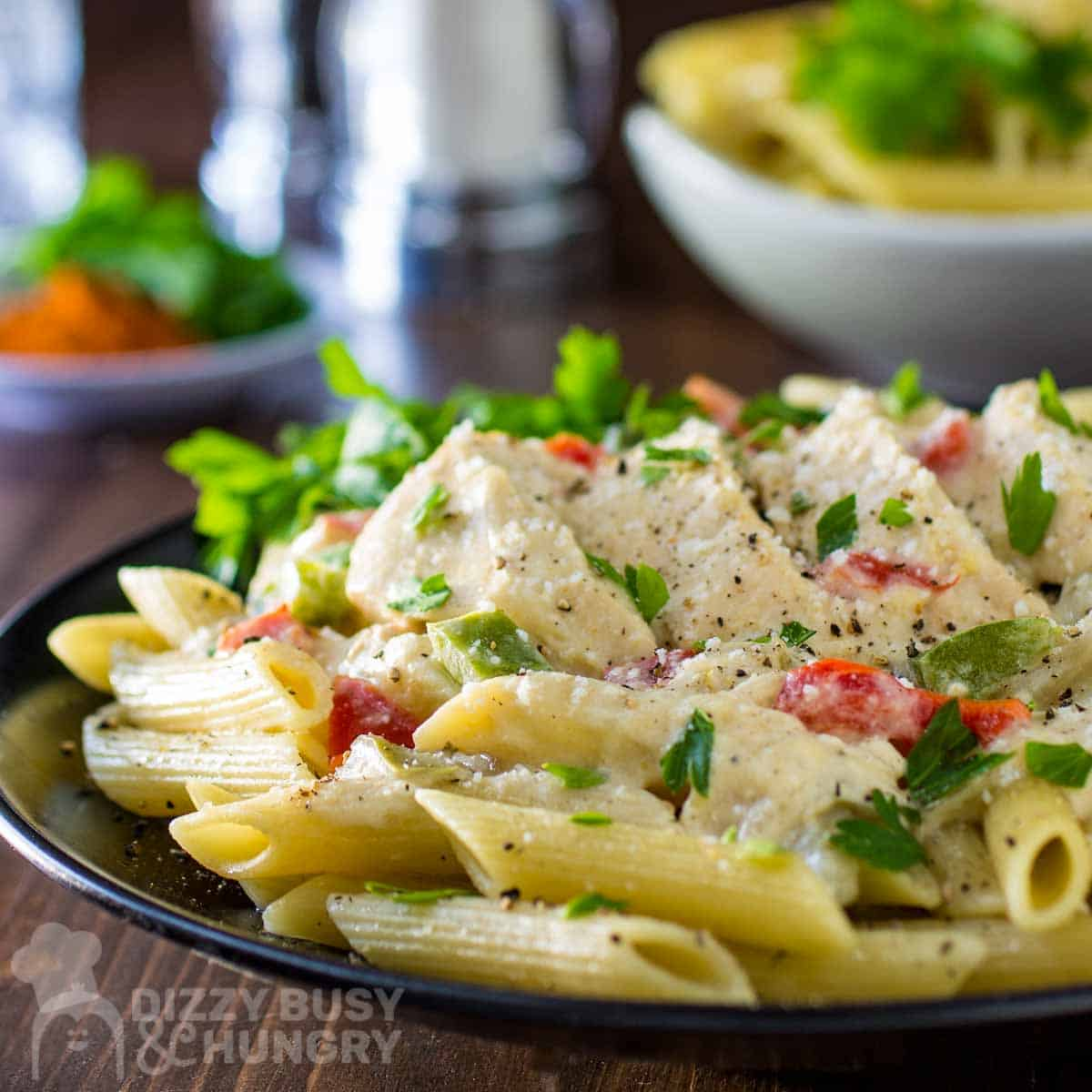Close up side view of creamy crockpot chicken on penne on a black plate with herbs on the side.