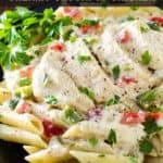 Close up view of creamy crockpot chicken on penne on a black plate with herbs on the side.