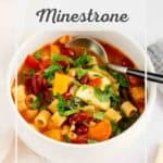 Minestrone soup in a white bowl with a spoon.