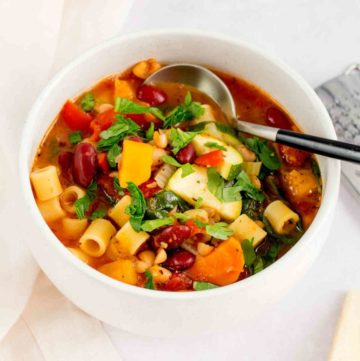 Close up of minestrone in a white bowl.