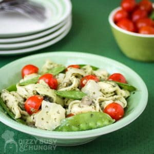 Side view of pesto tortellini in a green bowl with a bowl of grape tomatoes and plates in the background.