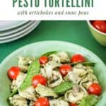 Overhead shot of pesto tortellini in a green bowl with a bowl of grape tomatoes and plates in the background.