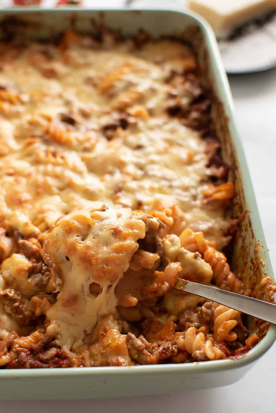 Cheesy hamburger casserole, with a spoon lifting up a serving.