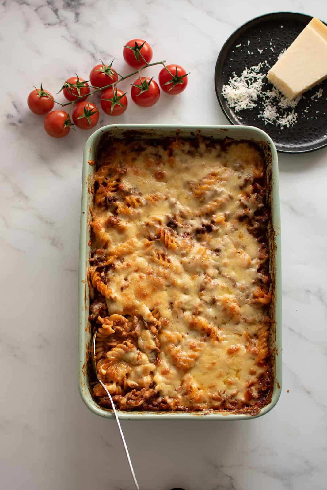 Hamburger casserole on a table, with cherry tomatoes and parmesan cheese on the side.