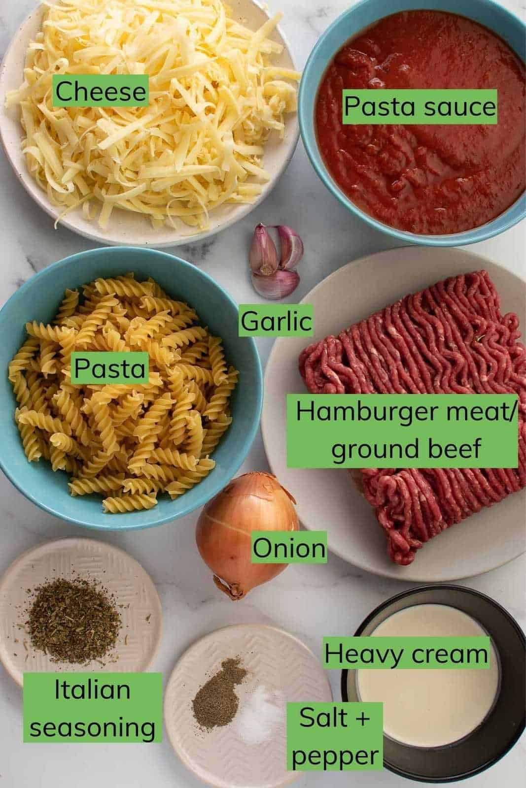 The ingredients required to make hamburger casserole laid out on a table.