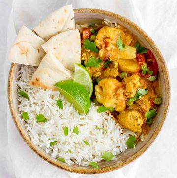 A bowl of rice with sliced naan, two lime wedges, and Instant Pot chicken curry.